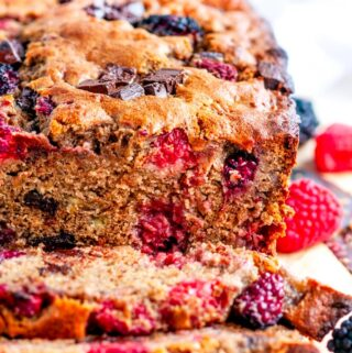 Chocolate Chunk Berry Banana Bread with knife on parchment paper
