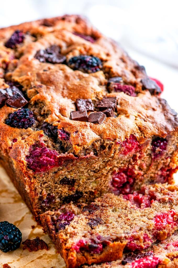 Chocolate Chunk Berry Banana Bread on parchment paper and white marble