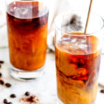 Cold Brew Coffee in tall glasses on white marble with tea towel