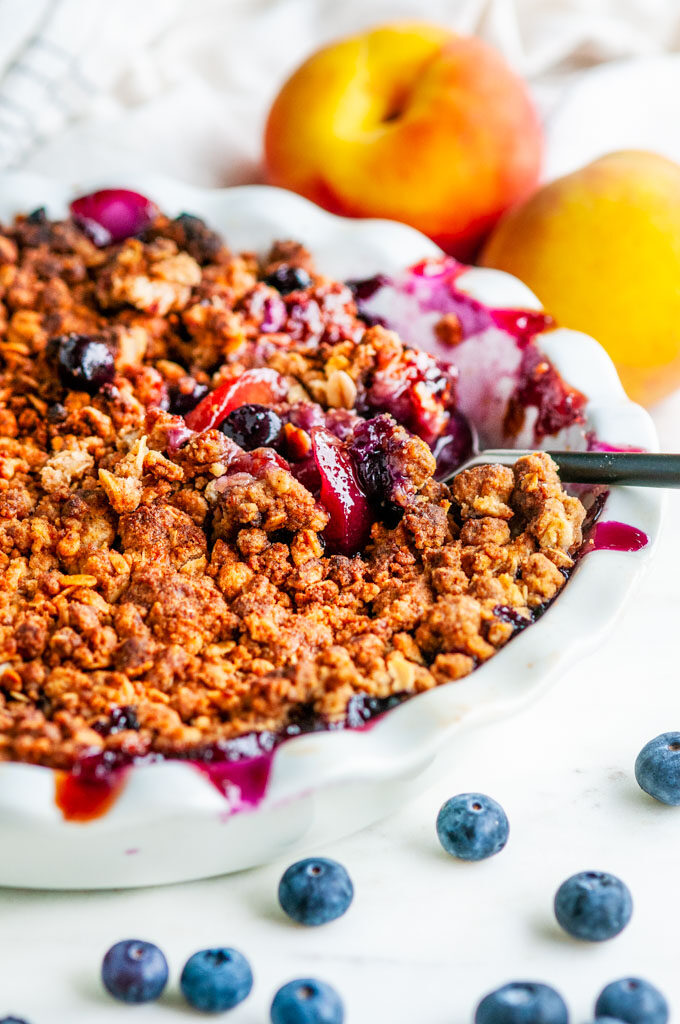 Easy Peach Blueberry Crisp in white pie pan with serving spoon on white marble