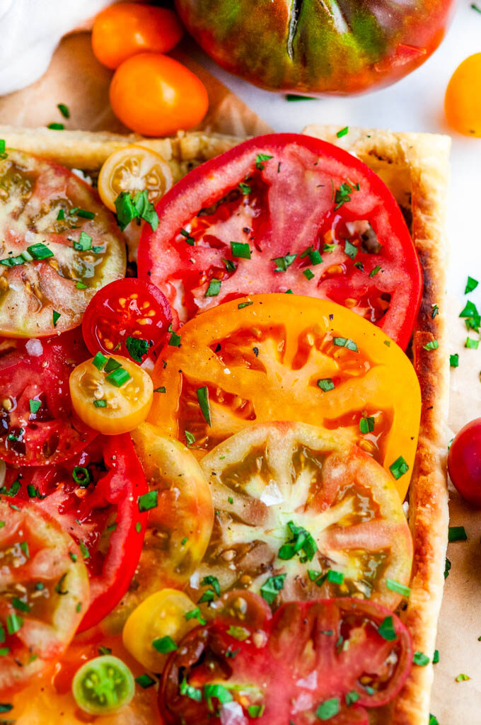 Heirloom Tomato Goat Cheese Tart on parchment paper and white marble