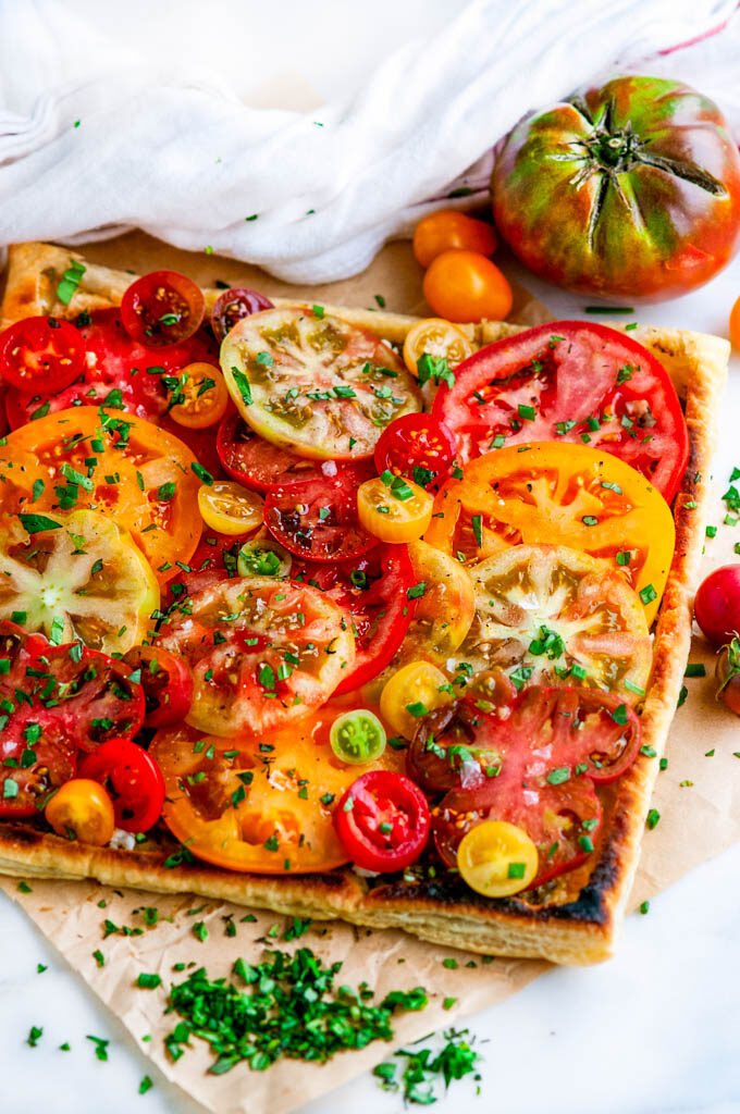 Heirloom Tomato Goat Cheese Tart on parchment paper and white marble with tea towel