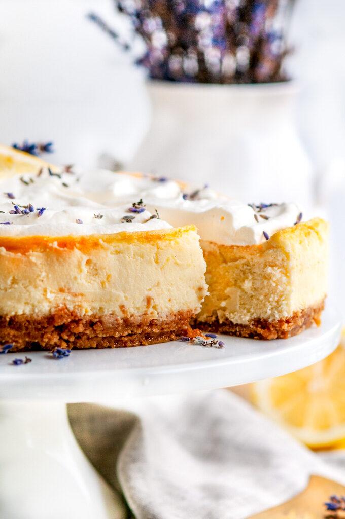 Lemon Lavender Mascarpone Cheesecake on white cake stand with slice