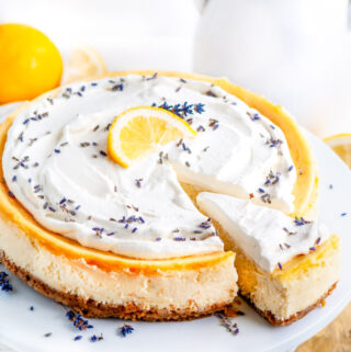 Lemon Lavender Mascarpone Cheesecake on white cake stand with slice and gold server