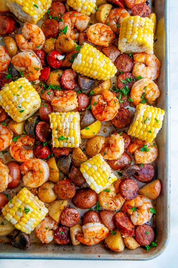 Sheet Pan Shrimp Boil with potatoes, andouille sausage, and corn on white marble