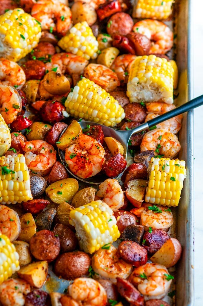 Sheet Pan Shrimp Boil with potatoes, andouille sausage, and corn on white marble with black spoon