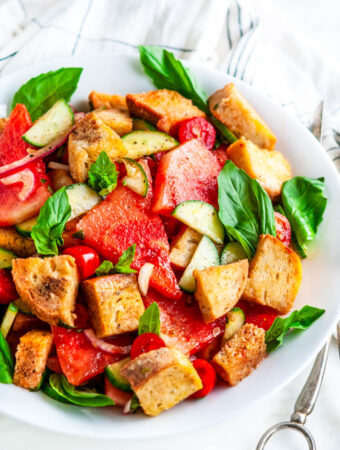 Watermelon Panzanella Salad in white bowl with silver serving tongs and tea towel