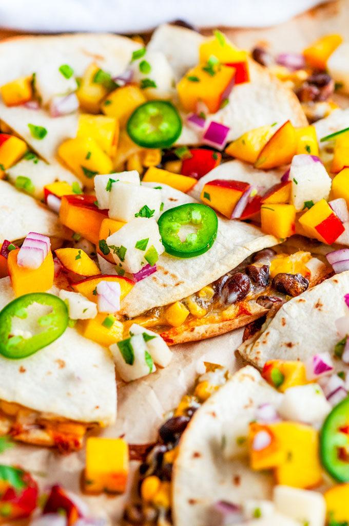 Cheesy Black Bean Quesadillas with Peach Jicama Salsa close up on parchment paper