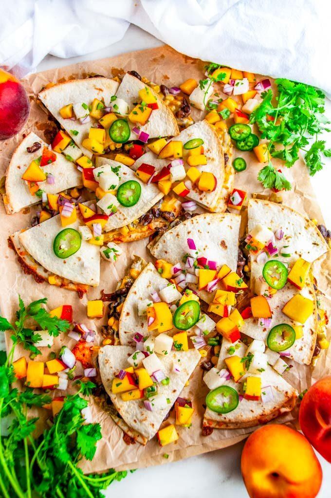 Cheesy Black Bean Quesadillas with Peach Jicama Salsa on parchment paper with cilantro