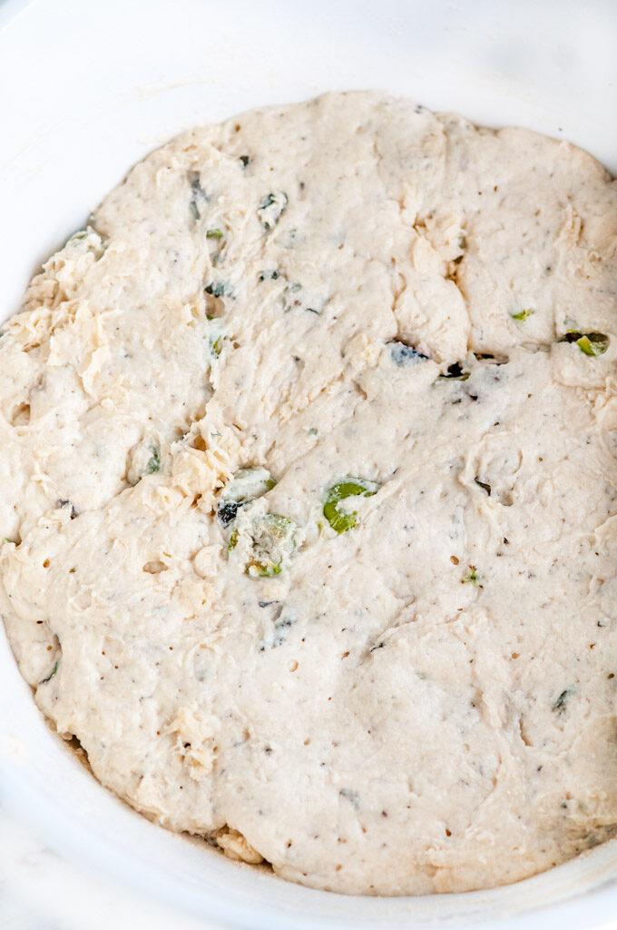 No knead olive bread dough in white bowl