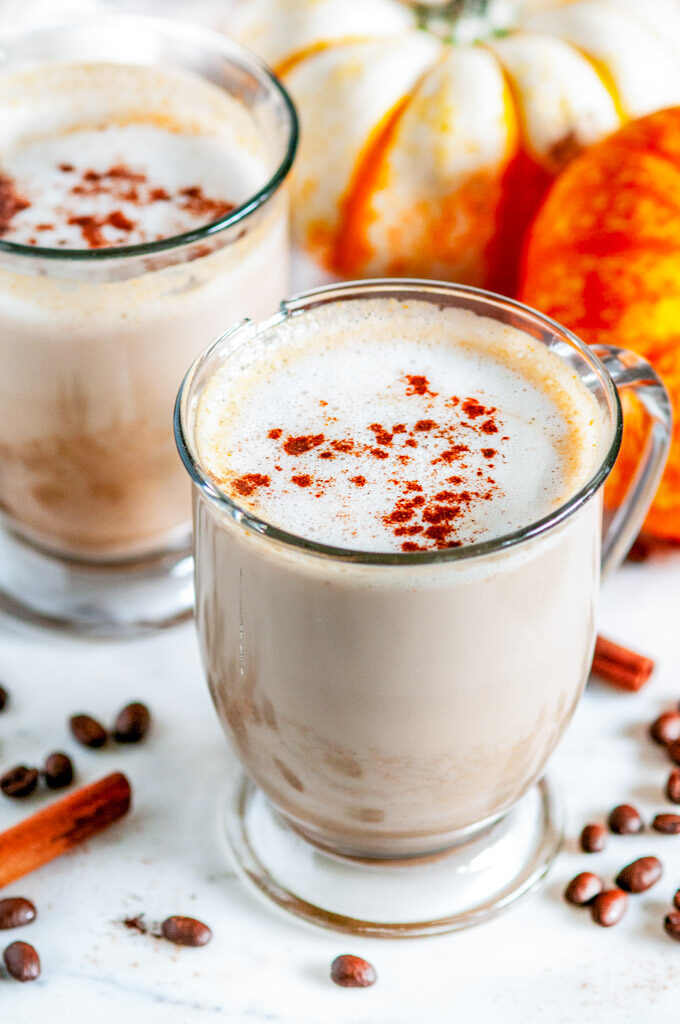 Pumpkin Spice Latte (with real pumpkin!) in glass mugs with coffee beans on white marble