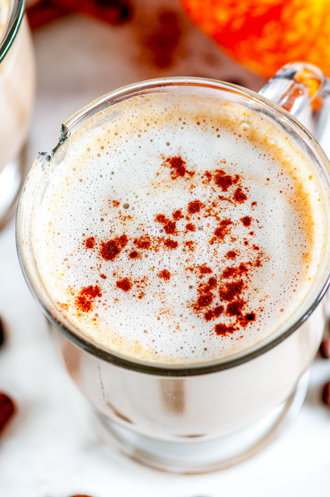 Pumpkin Spice Latte (with real pumpkin!) in glass mug close up with coffee beans on white marble