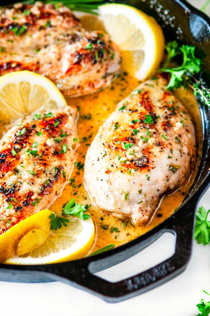 Skillet lemon garlic butter chicken in lodge cast iron skillet with lemons and herbs on white marble