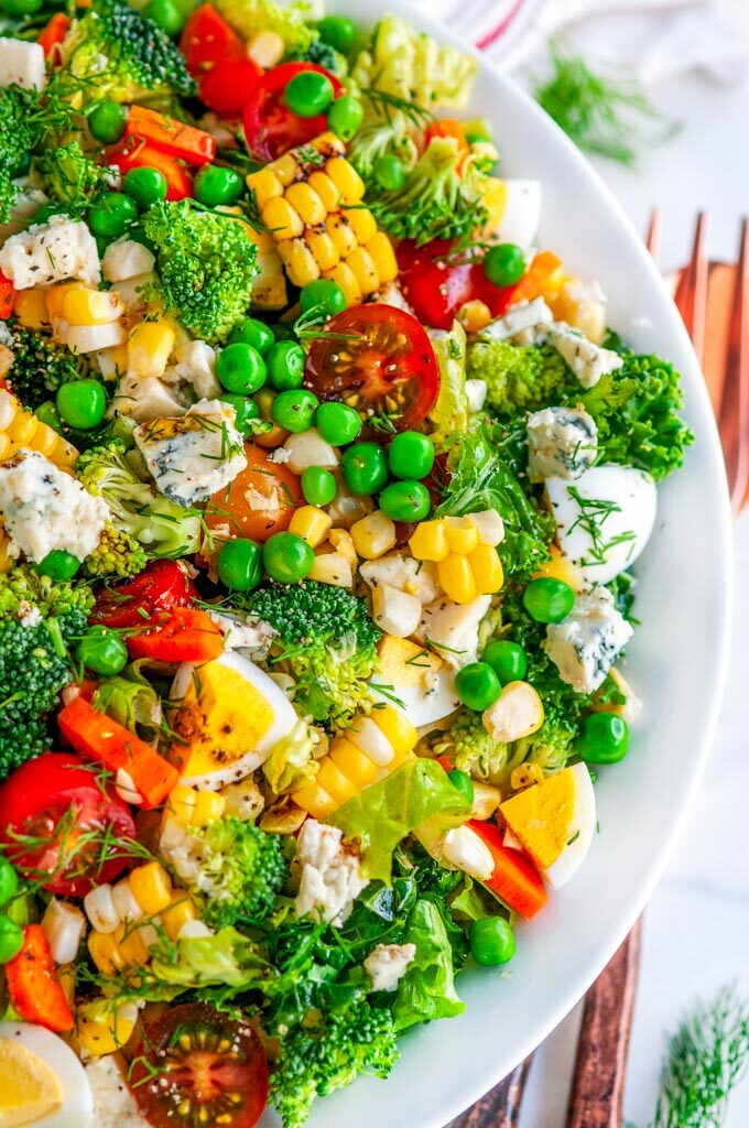 Summer Harvest Chopped Veggie Salad in white bowl with copper serving utensils on white marble