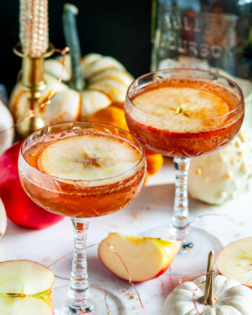 Autumn Apple Cider Whiskey Cocktail in glasses white marble with pumpkins