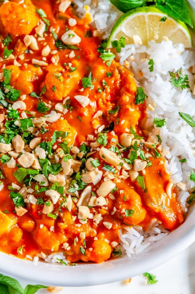 Caulfilower Sweet Potato Coconut Curry with jasmine rice, cilantro, and limes in white bowl on marble close up