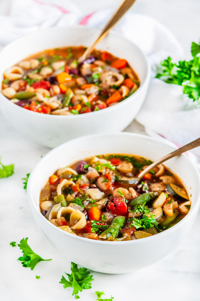 Easy classic minestrone soup in white bowls with gold spoons and fresh parsley on white marble