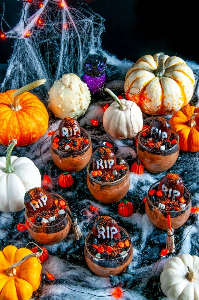 Death By Chocolate Mousse Graveyard Pots in glass on black fabric with spider webbing and pumpkins