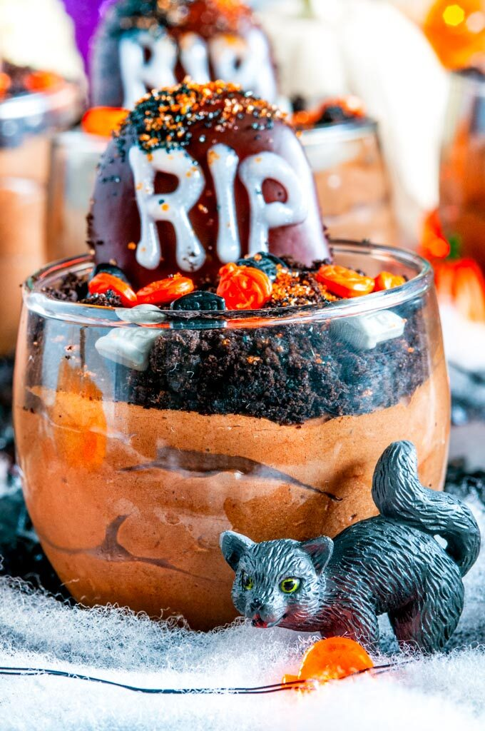 Death By Chocolate Mousse Graveyard Pots in glass on black fabric with spider webbing, pumpkins, and black cat close up