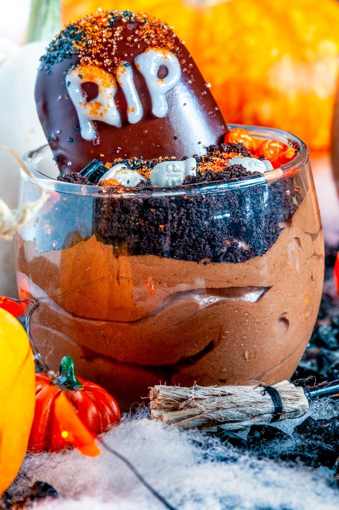 Death By Chocolate Mousse Graveyard Pots in glass on black fabric with spider webbing and pumpkins close up