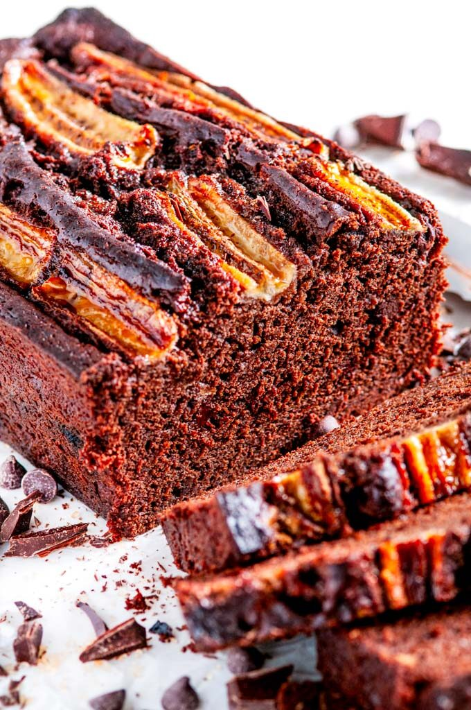 Double Chocolate Banana Bread loaf and slices with chocolate chunks and knife on white marble close up