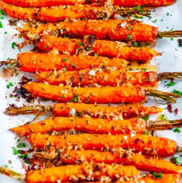 Garlic Parmesan Roasted Carrots with fresh parsley on parchment paper
