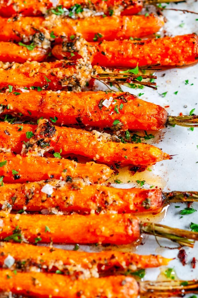 Garlic Parmesan Roasted Carrots with fresh parsley on parchment paper close up