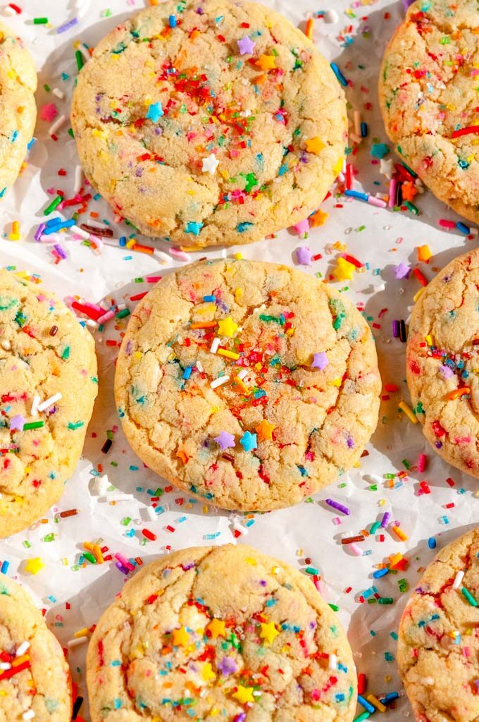 Soft Chewy Funfetti Cookies with rainbow sprinkles and sanding sugar on parchment paper