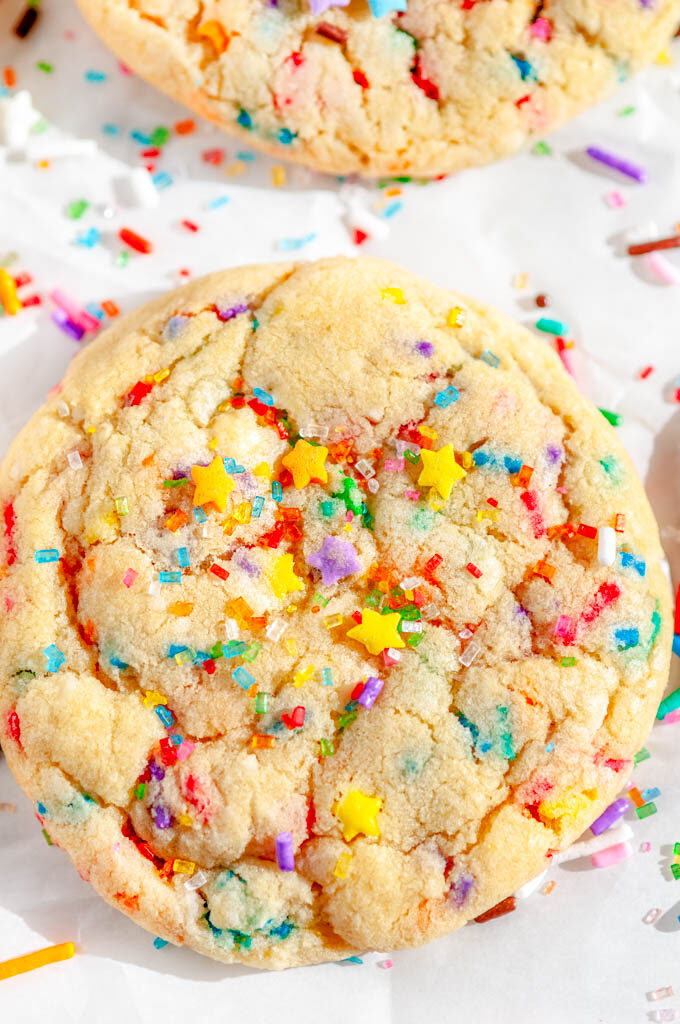 Soft Chewy Funfetti Cookies with rainbow sprinkles and sanding sugar on parchment paper close up