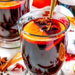 Spiced Holiday Mulled Wine in glass mugs with gold spoons, orange slices, star anise, cinnamon sticks, and maple leaves