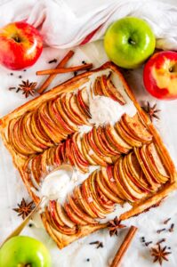 Chai Spice Apple Galette with vanilla ice cream, star anise, and cinnamon sticks on white marble