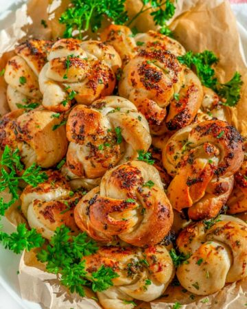 Herb Garlic Parmesan Knots with parsley on white platter