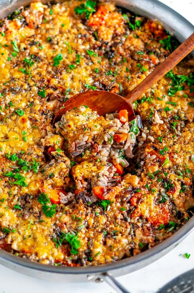 One Pot Turkey Wild Rice Casserole in all clad skillet with wooden spoon on white marble close up