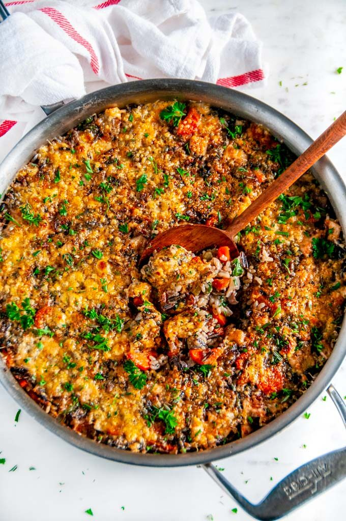 One Pot Turkey Wild Rice Casserole in all clad skillet with wooden spoon on white marble