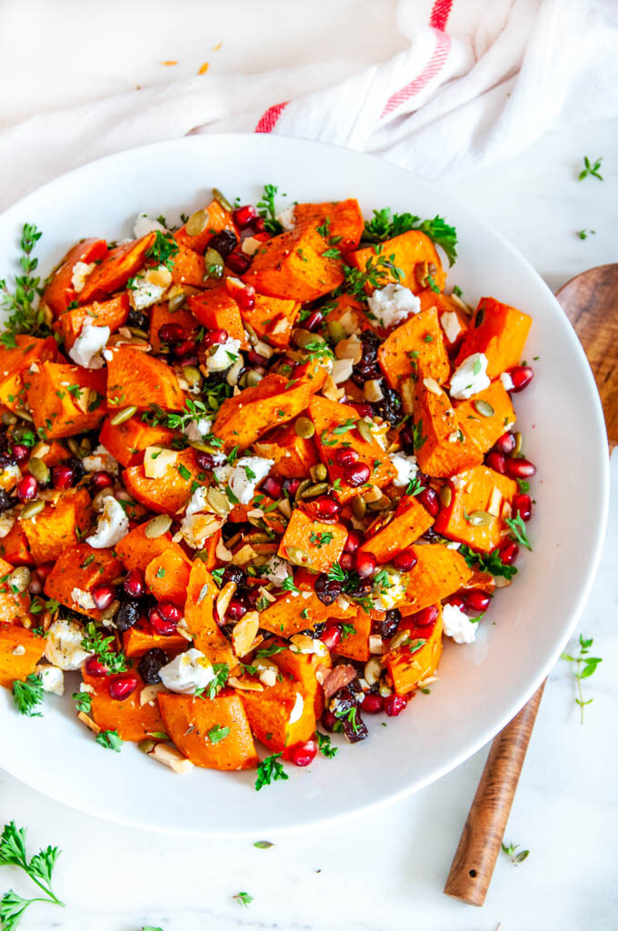 Roasted Sweet Potato Salad in white bowl on marble with wood spoon