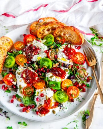 Tomato Pomegranate Burrata Salad on gray plate with gold spoon on white marble with tea towel