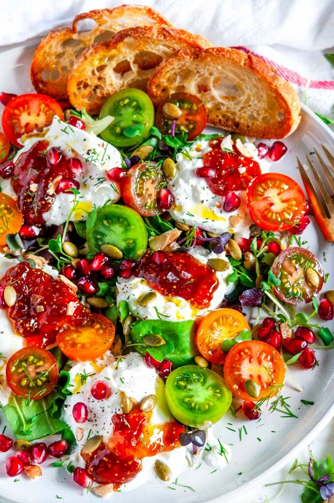 Tomato Pomegranate Burrata Salad on gray plate with gold fork close up