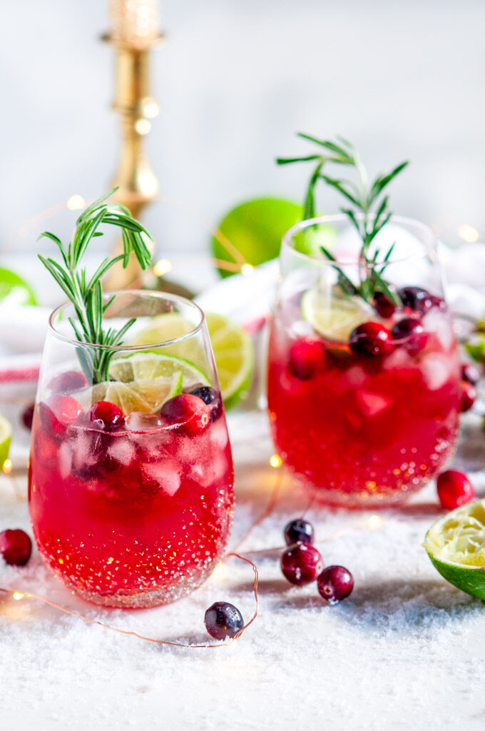 Yuletide Cranberry Moscow Mule with rosemary and limes on white marble with gold candle