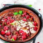 Chocolate Dutch Baby with whipped cream, chocolate sauce, rasperries, mint, pomegranate arils, and powdered sugar in lodge cast iron skillet on white marble