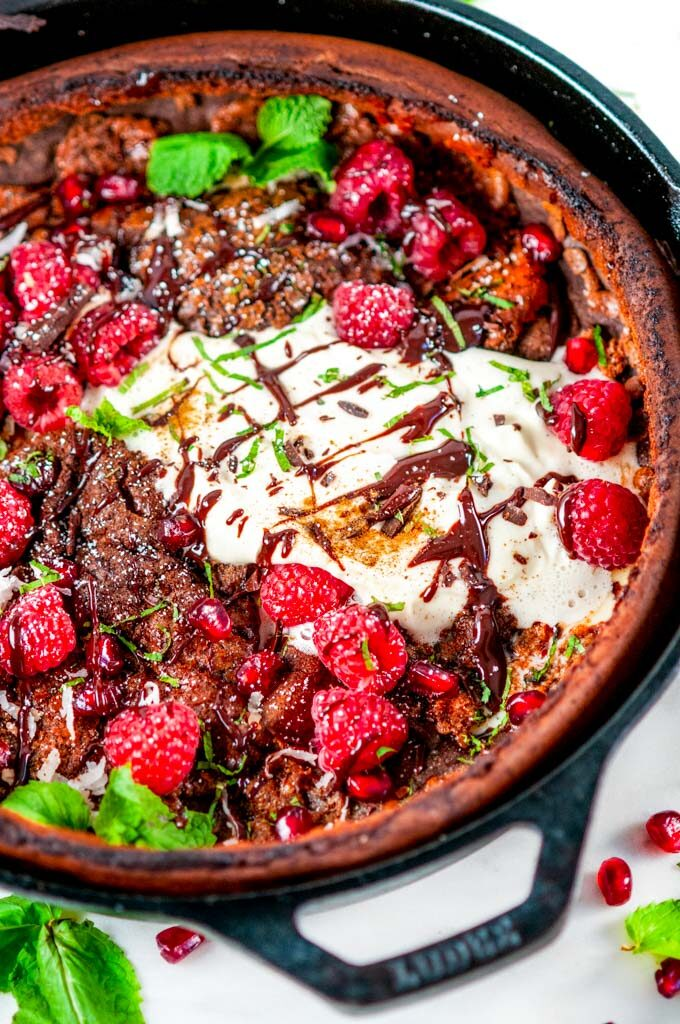 Chocolate Dutch Baby with whipped cream, chocolate sauce, rasperries, mint, pomegranate arils, and powdered sugar in lodge cast iron skillet on white marble close up