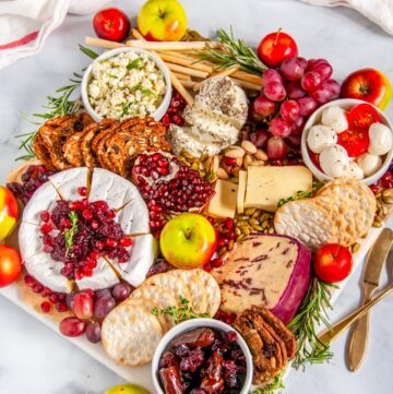 Festive Winter Cheese Board on marble with gold knife and spoon