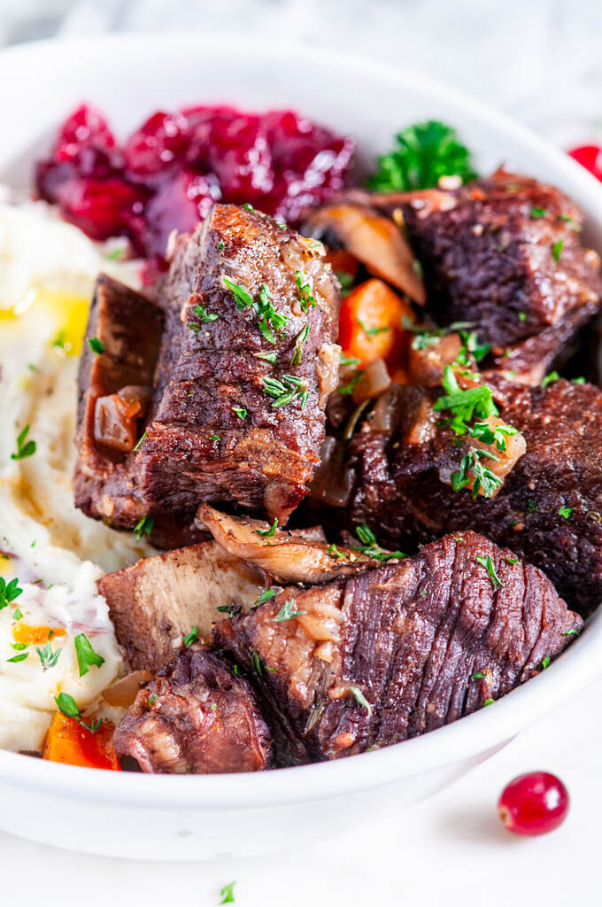 Instant Pot Red Wine Braised Short Ribs with mashed potatoes and cranberries in a white bowl close up