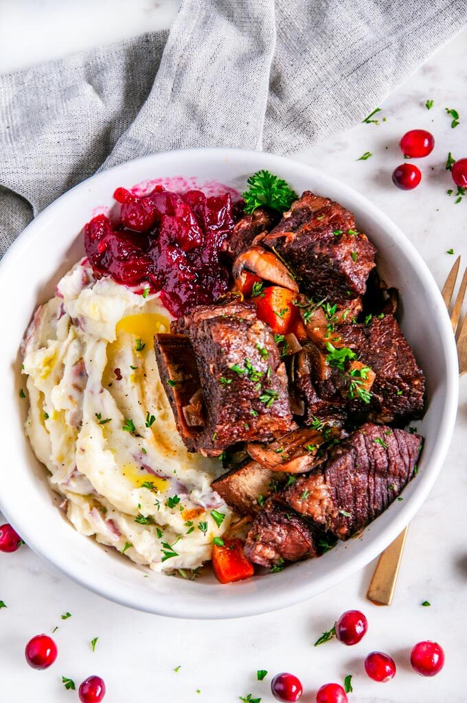 Instant Pot Red Wine Braised Short Ribs with mashed potatoes and cranberries in a white bowl