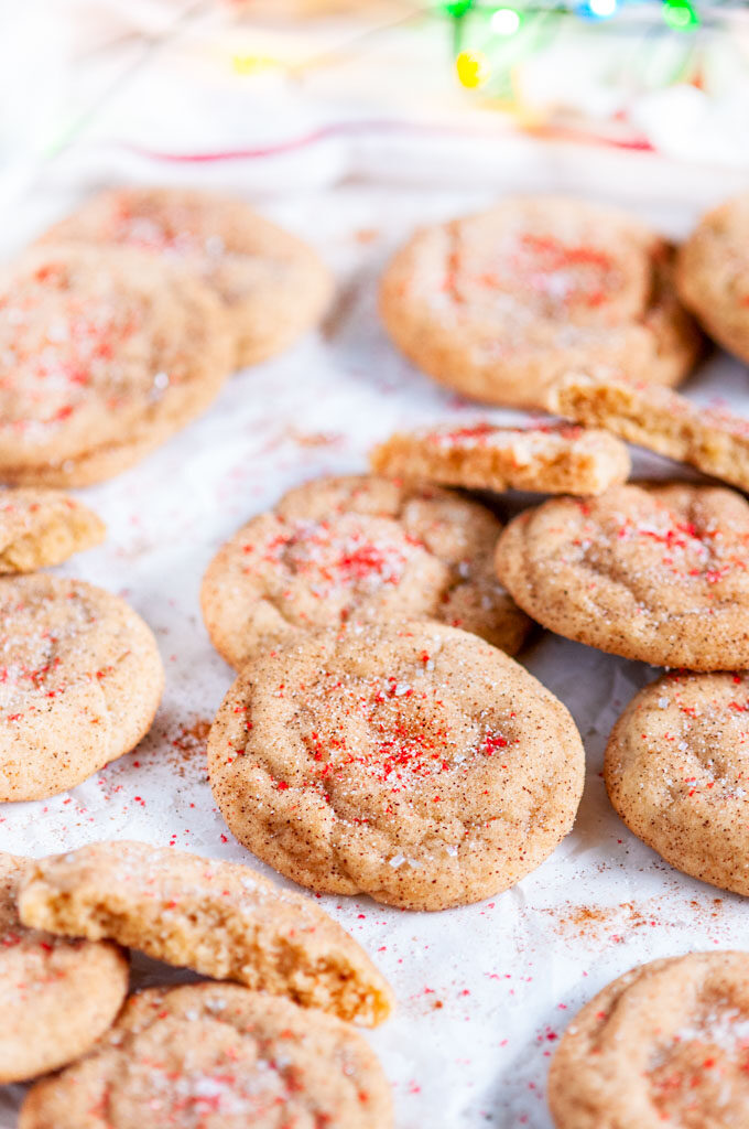 Soft Chewy Snickerdoodles on white parchment with red sanding sugar and christmas lights