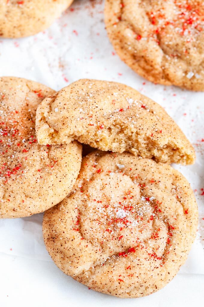 Soft Chewy Snickerdoodles on white parchment with red sanding sugar close up