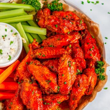 Crispy Buffalo Chicken Wings (Air Fryer + Oven Baked Methods) with carrots, celery and blue cheese dressing close up