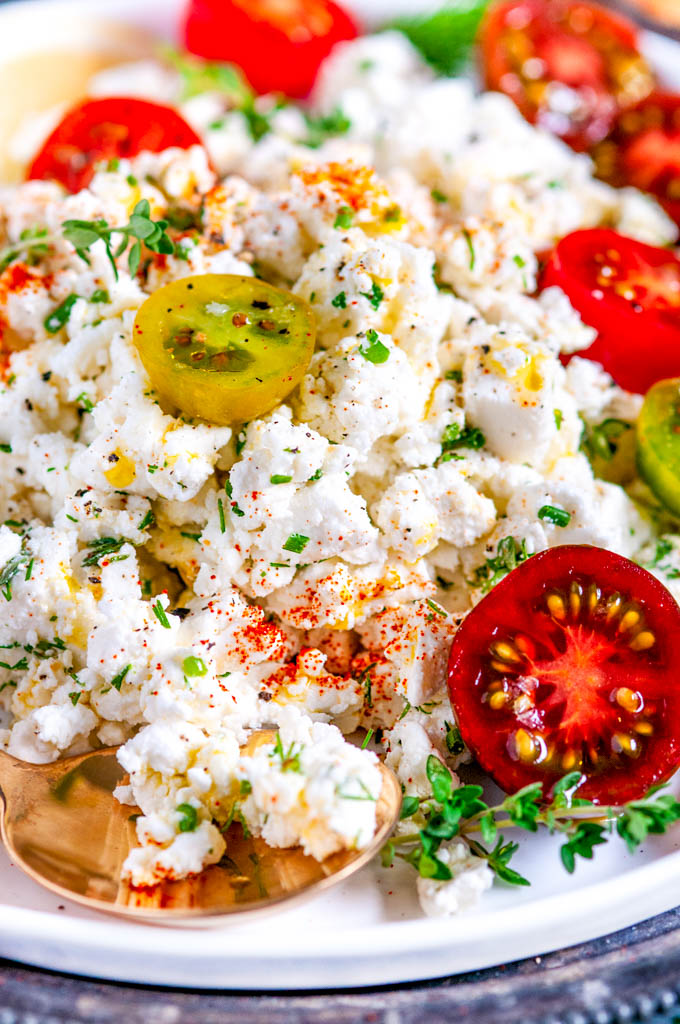 Easy Crumbled Feta Cheese Dip with cherry tomatoes lemon and thyme on white plate close up