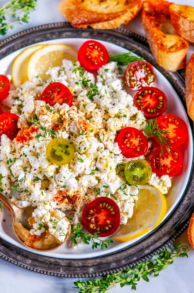 Easy Crumbled Feta Cheese Dip with cherry tomatoes lemon thyme and gold spoon on white plate