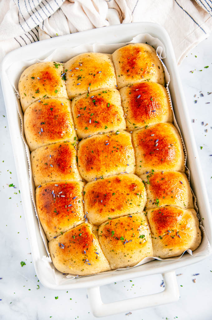 Honey Lavender Herb Dinner Rolls in white baking dish with parchment baked with tea towel on white marble