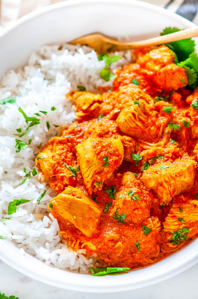 Instant Pot Chicken Tikki Masala in white bowl with basmati rice and cilantro close up